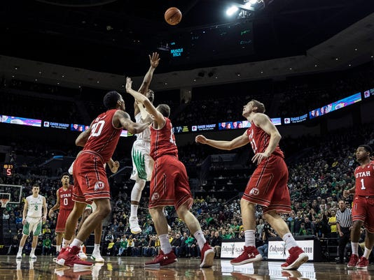 CORRECTS TO FRIDAY, INSTEAD OF SATURDAY - Oregon forward Mikyle McIntosh (22) shoots over Utah defenders during the first half in an NCAA college basketball game Friday, Dec. 29, 2017, in Eugene, Ore. (AP Photo/Thomas Boyd)