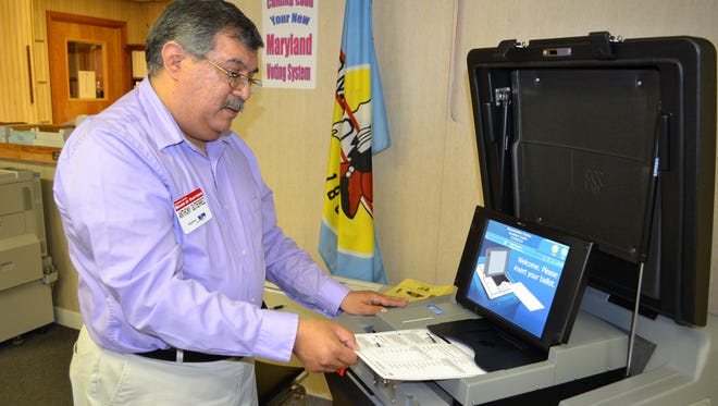 Anthony Gutierrez, elections director for Wicomico County, shows how to feed a paper ballot into a scanning unit. The new voting machines will be used across the state during the Maryland Primary on Tuesday, April 26.