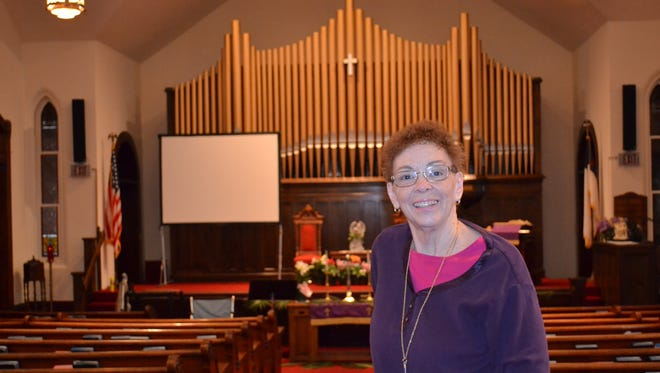 Pastor Christine Tobergte stands in the historic sanctuary inside the 125-year-old Green Springs United Methodist Church. Tobergte is the most recent of a long string of pastors who have ministered at the church, beginning with circuit preachers in the 19th century.