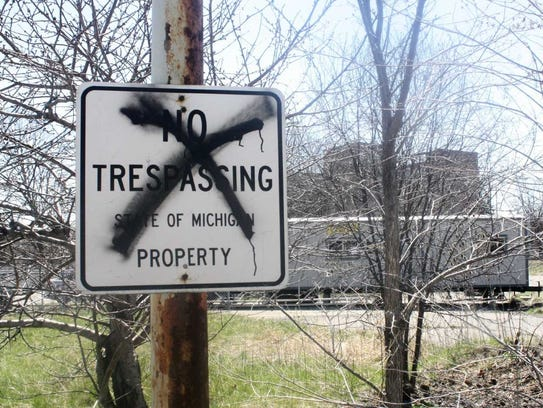 A vandalized no trespassing sign stands on the perimeter of the hospital site.