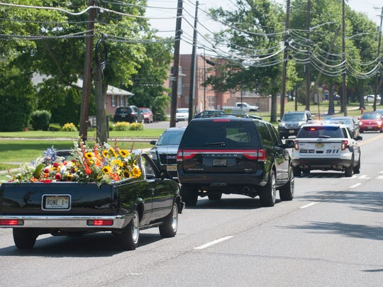 A funeral procession drives down East Chestnut Avenue