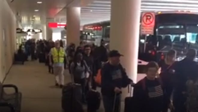 Passengers wait in line to board buses at Southwest Florida International Airport on Friday. The buses were heading to Fort Lauderdale. Airplanes flying into Fort Lauderdale on Friday were diverted to other airports in the state after a shooting at the Fort Lauderdale airport left 5 dead.