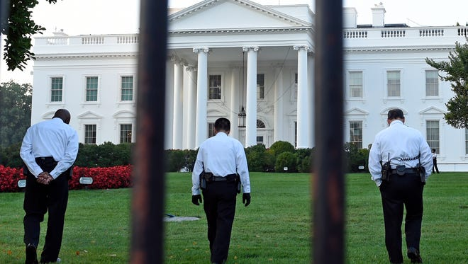 Uniformed Secret Service officers walk along the lawn on the North side of the White House in Washington, Saturday, Sept. 20, 2014. The Secret Service is coming under renewed scrutiny after a man scaled the White House fence and made it all the way through the front door before he was apprehended.