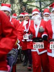 Runners dressed as Santa Claus begin their race down