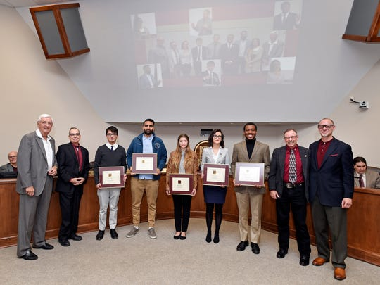 New Mexico State University Chancellor Garrey Carruthers, far left, is accompanied by the vice president for Economic Development Kevin Boberg, second from left, assistant professor of International Relations Neal Rosendorf, far right, and Regents professor Thomas Dormody, second from right, in recognizing Domenici Student Scholars, from left, Daniel Estupinan, Harris Ahmed, Katelynn Goodman, Ana Lopez and DeLorean Forbes during a Board of Regents regular meeting.