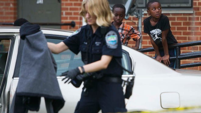 Children stand nearby as a member of the Knoxville Police Department investigates a shooting which occurred near East New Street and Burge Drive by the Austin Homes Apartments in East Knoxville Saturday, July 1, 2017. This is the second shooting which occurred in East Knoxville today.