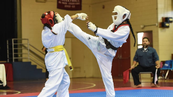In this file photo, Chastity Tenorio, right, lands a front kick for a full point at the Shinkyokushinkai 2016 Guam National Full Contact Karate Championship at St. John's School.