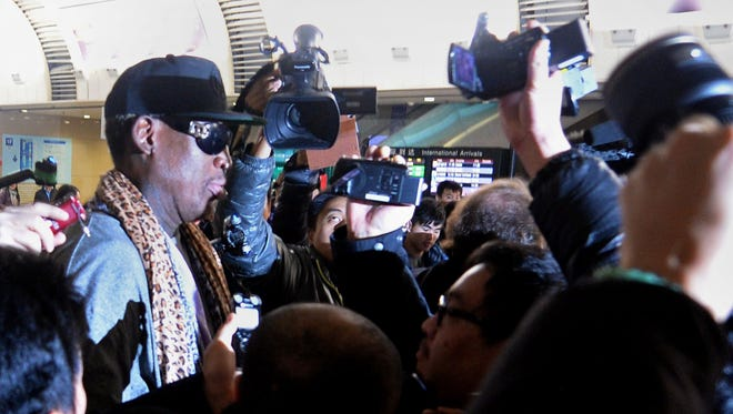 Former NBA star Dennis Rodman is mobbed by journalists on his arrival back from Pyongyang, at Beijing's international airport on Monday.