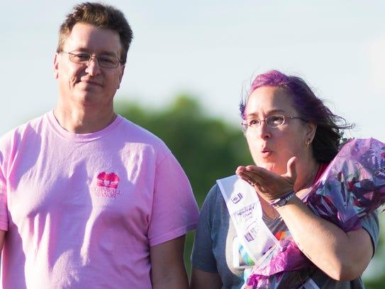 Cancer survivor Gretchen Neiswender (right) blows a
