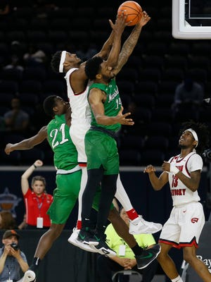 Western Kentucky Hilltoppers guard Josh Anderson (4) grabs a rebound against Marshall Thundering Herd forward Darius George (21) and guard C.J. Burks (14) during the Conference USA Tournament at Ford Center at The Star.