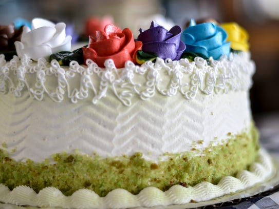 A pistaccio cake is adorned with colorful frosting