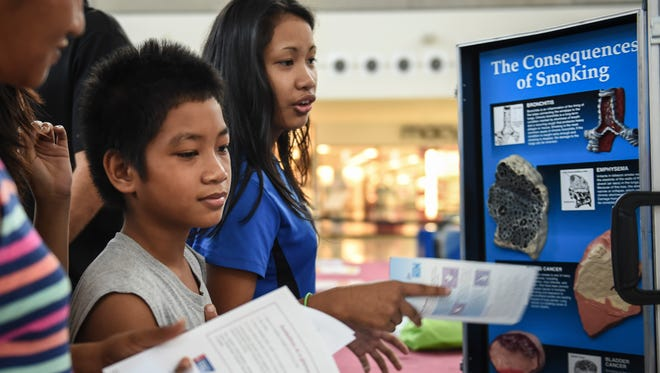 Julian Bilon, 11, of Dededo, learns about the consequences of smoking with his family at the Breast Cancer Awareness Month Proclamation Signing and Wellness Event at the Micronesia Mall on Sept. 30.
