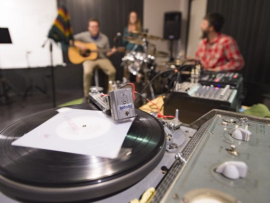 People cut a vinyl at the Music District opening party Friday, September 30, 2016. The location, at 639 S. College Avenue, aims to become a workspace and creative hub for musicians in Northern Colorado.