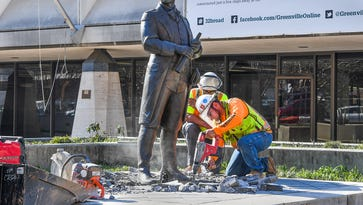 Frank Keller, front, and  Barry Harling break the concrete around the base of the statue of Revolutionary War general Nathanael Greene on the plaza of old The Greenville News building on Main St. in downtown Greenville on Monday, March 21, 2017. The statue is being prepared to be moved into storage either later this week or early next week.