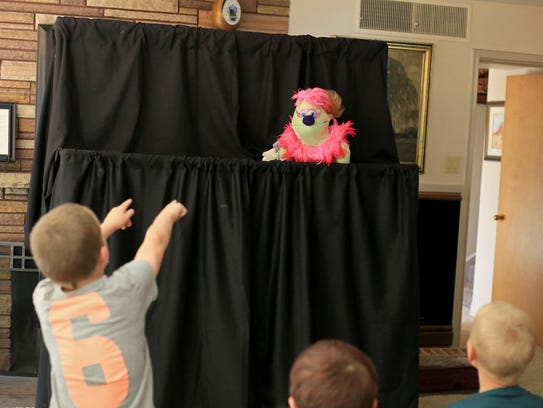 A child interacts with a puppet during a show March