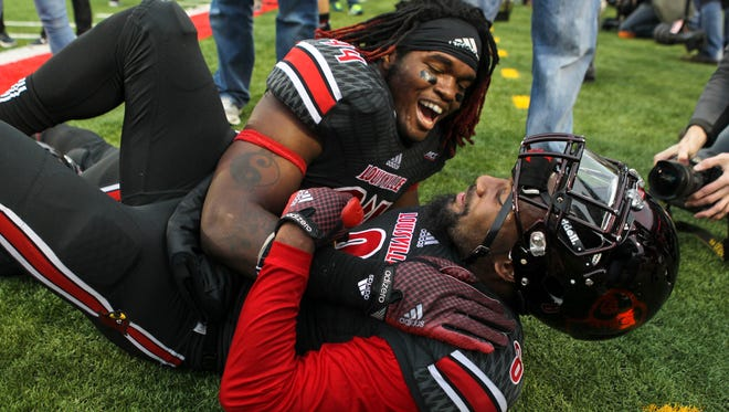 Louisville's Lorenzon Mauldin celebrates with teammate Gerold Holliman after the Cards beat Kentucky 44-40 to win the Governor's Cup Saturday at Papa John's Cardinal Stadium. Nov. 29, 2014 By Matt Stone/The C-Jd
