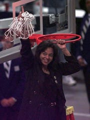 Purdue coach Carolyn Peck holds up the net after her team won the Championship game of the Women's Final Four in San Jose, Calif., Sunday, March 28, 1999. Purdue beat Duke 62-45.