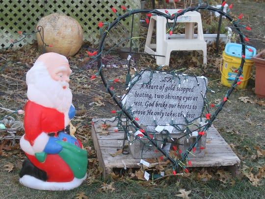 A Santa Claus kneeling before a memorial plaque, honoring