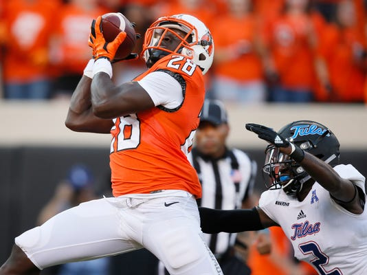 FILE - In this Aug. 31, 2017, file photo, Oklahoma State wide receiver James Washington (28) catches a pass for a touchdown, in front of Tulsa cornerback Kerwin Thomas (2) during the first half of an NCAA college football game in Stillwater, Okla. Oklahoma State faces Texas Tech this week in a matchup of the Big 12's top two passing teams. (AP Photo/Sue Ogrocki, File)