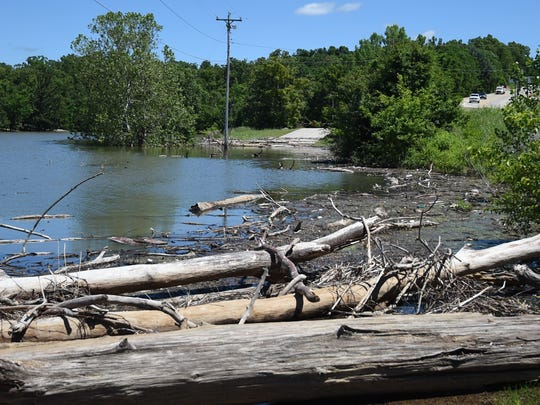 The road leading to the the Henderson Recreation Area and Campground is blocked Thursday by debris and the elevated water of Norfork Lake. The Army Corps of Engineers has closed parks at Henderson, Pigeon Creek, Tecumseh and Udall for the weekend.