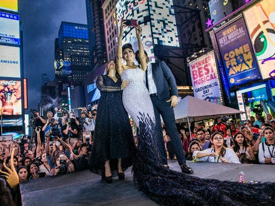 Shilpa Shetty, center, takes a selfie as she participates of a fashion show during The 18th edition of the International Indian Film Academy (IIFA) awards weekend event at Times Square on Thursday, July 13, 2017, in New York.