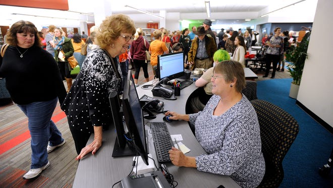 Judie Eichorst (center) gets help finding a book from librarian assistant, Cynthia Gault, during the opening of the Abilene Public Library's new south branch location at the Mall of Abilene on Saturday, Nov. 19, 2016.