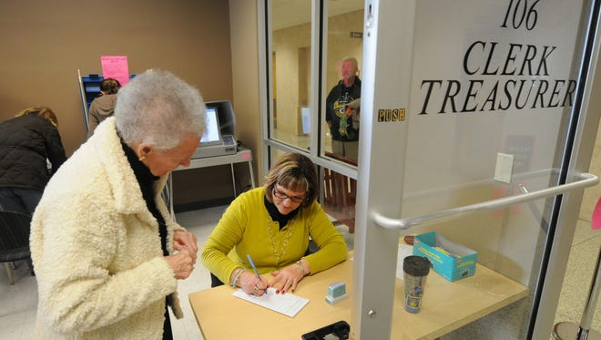 Voter Nancy Waller, left, turns in her voter form with help from poll worker Dawn Canadeo in October 2012.