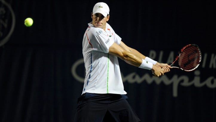 John Isner  returns a shot from Mikhail Kukushkin of Kazakhstan during the Winston-Salem Open.