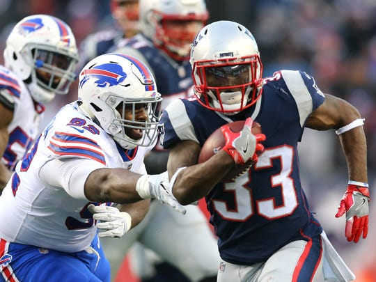 Dion Lewis of the New England Patriots evades a tackle by a Buffalo Bills player during the first half at Gillette Stadium on December 24, 2017, in Foxborough, Massachusetts.