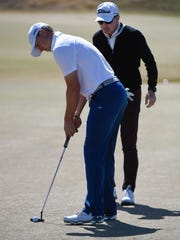 Jordan Spieth, left, putts during practice in front