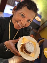 Mama Irma owner and chef Hilda Cano holding one of her tasty alfajores, a caramel sandwich cookie.