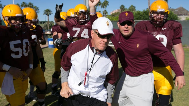 ASU assistant head coach/ offensive line Chris Thomsen (center) and Josh Martin, an ASU graduate assistant (right) break a huddle with the ASU offensive line players during Spring practice at the Kajikawa practice fields at ASU  in Tempe on Thursday, April 3, 2014.