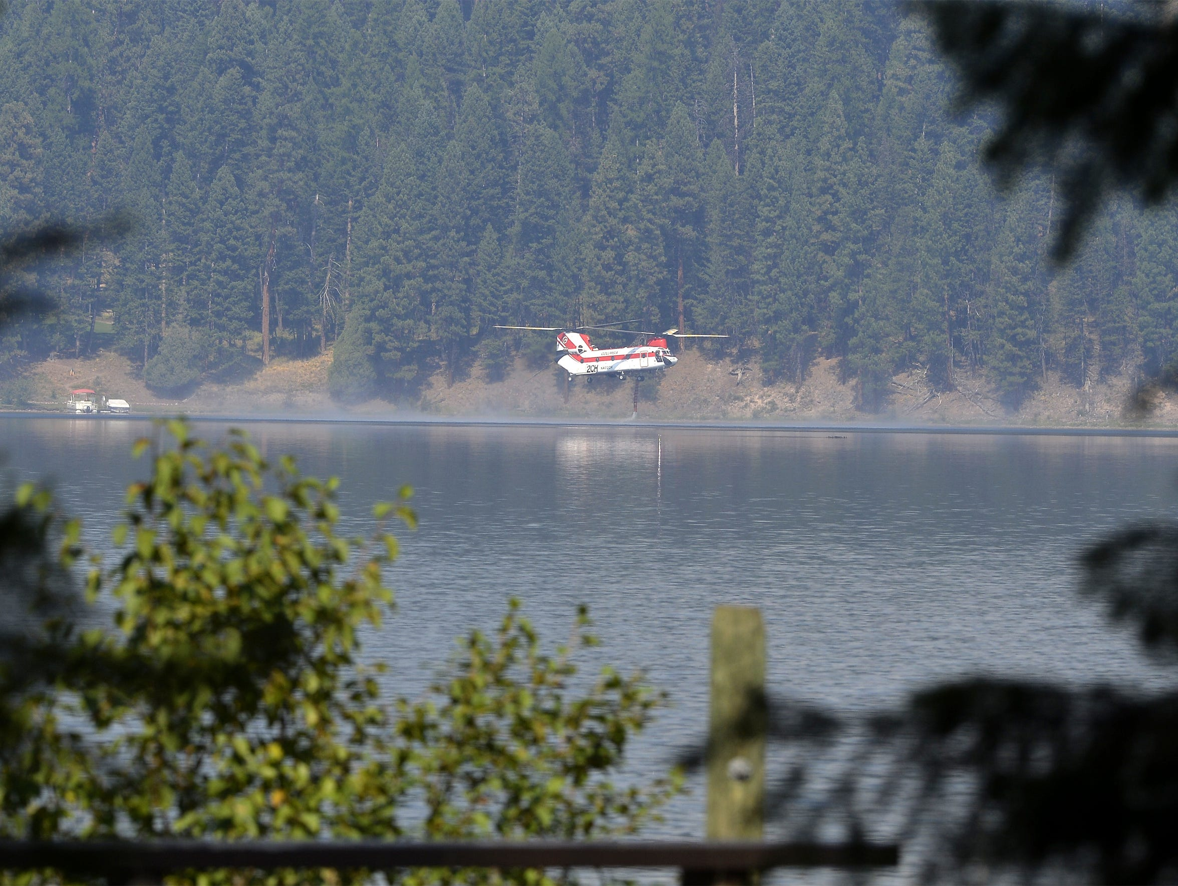 A Chinook helicopter fills up on water in Seeley Lake