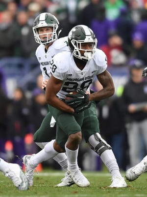 Michigan State running back Madre London (28) runs the ball next to quarterback Brian Lewerke (14) during the first half of MSU's 39-31 triple-overtime loss on Saturday, Oct. 28, 2017, in Evanston, Ill.