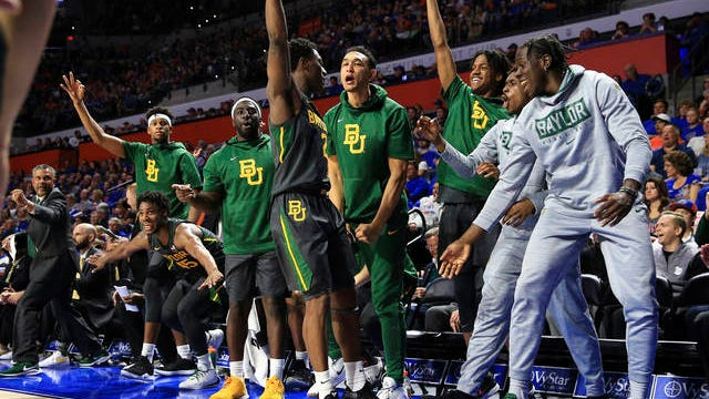 Baylor guard Devonte Bandoo (2) celebrates with teammates on the bench after scoring a three-point basket during the second half of an NCAA college basketball game against Florida on Jan. 25 in Gainesville, Fla.