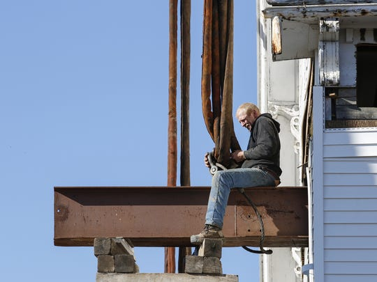 A worker secures the custom-fabricated I-beams to the crane so the roof will be safely lifted off the building Tuesday, Feb. 21, in Newton.