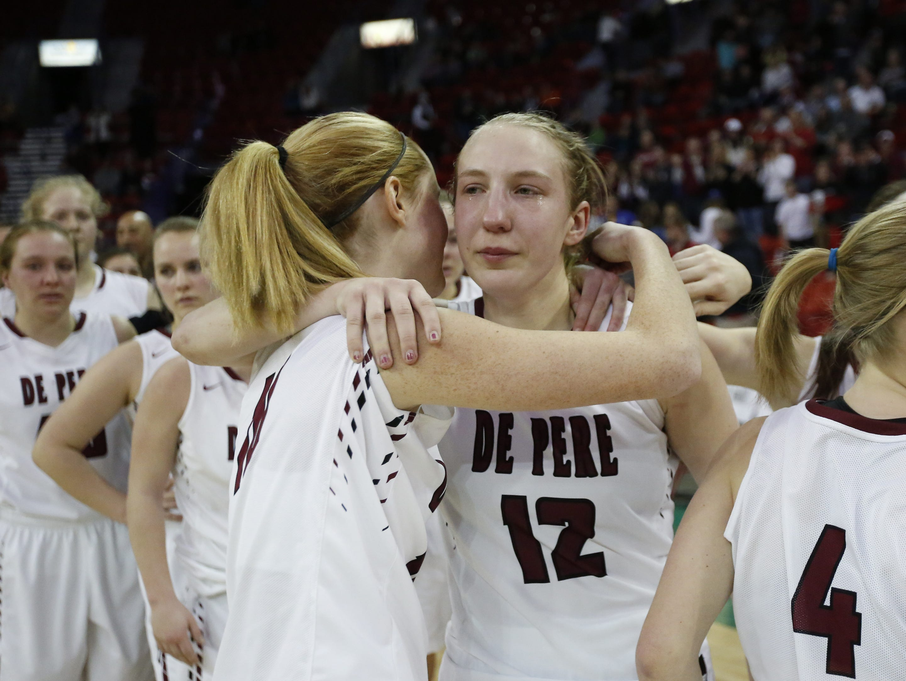De Pere's Lizzie Miller hugs teammate Lauren DeMille after their loss to Appleton North in the WIAA Division 1 State Tournament girls basketball championship game Saturday at the Resch Center.