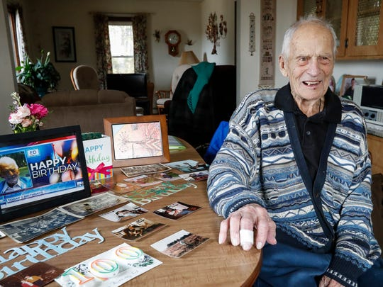 Ed Shimon in his home next to photographs of himself throughout the years Wednesday, March 21, in Manitowoc. Shimon celebrated his 100th birthday this year.