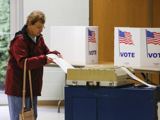 In this file photo, voter Janet Jilek inserts her paper