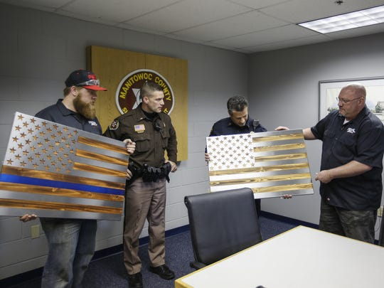 Metal Art of Wisconsin's Eric Machia, left, and Shane Henderson, right, present Lt. Dan Hartwig, middle left, and Capt. Larry Zimney with the flags Henderson and Metal Art of Wisconsin donated to the Manitowoc County Sheriff's and Manitowoc Police departments April 28 in Manitowoc.
