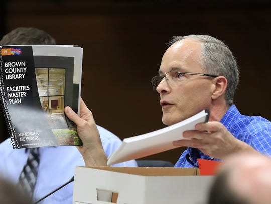Brown County Supervisor John Van Dyck holds up copies