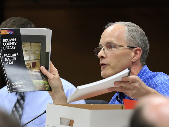 Brown County Supervisor John Van Dyck holds up copies of previous county studies at a Brown County Board of Supervisors meeting at City Hall on Wednesday, May 17, 2017, in Green Bay, Wis.