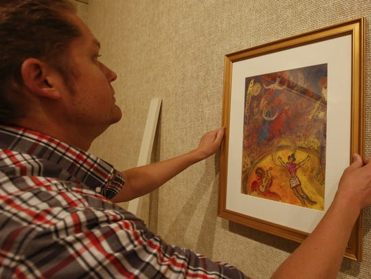 Rahr-West curator Adam Lovell hangs a print from Marc