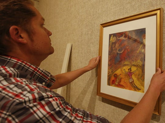 Rahr-West curator Adam Lovell hangs a print from Marc