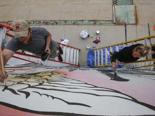Local artists and collaborators David Carpenter and Erin LaBonte work on the new mural on the 10th Street bridge June 13 in Manitowoc.