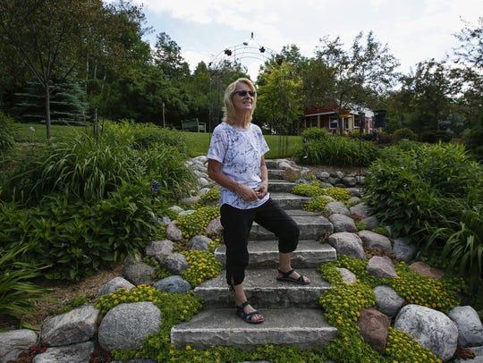 Kris Cisler poses for a photo in her garden June 21