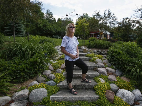 Kris Cisler poses for a photo in her garden June 21 in Manitowoc.