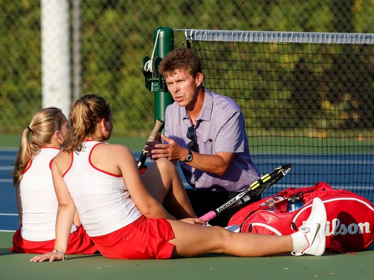 FILE - Manitowoc Lincoln's varsity tennis coach Jacques Verbauwhede talks to doubles team Caroline Ramminger and Isabella Wergin in between sets in a close doubles match against Notre Dame at Lincoln Park Sep. 12, 2017.