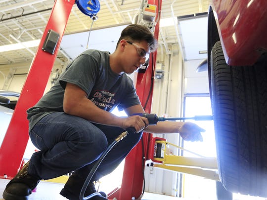 Green Bay East junior Ivan Gonzalez changes a tire during a City Stadium Automotive class at East High School on Thursday, September 14, 2017 in Green Bay, Wis. The class is part of the Turbocharge with College Credit initiative, launched earlier this year in Green Bay Public schools. The initiative aims to have every high school student graduating with at least 15 college credits. Adam Wesley/USA TODAY NETWORK-Wisconsin