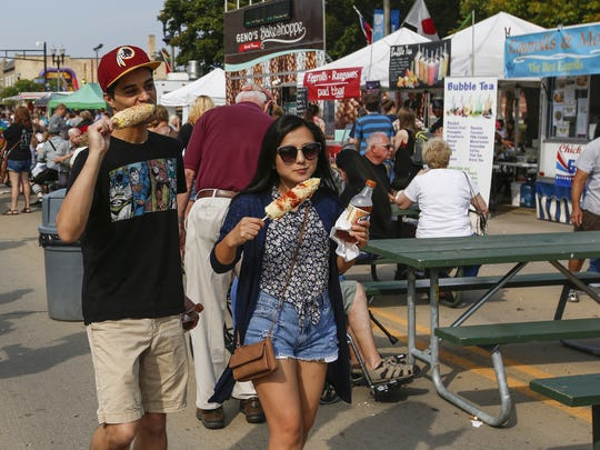 File - Daniel Dyer and Sheng Yang eat Elotes, a Mexican
